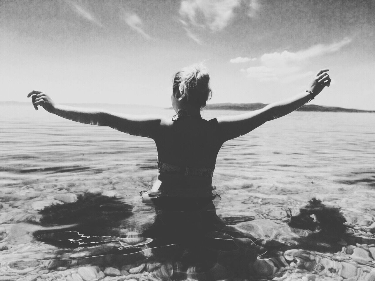 Rear View Of Young Woman With Arms Outstretched In Sea Against Sky