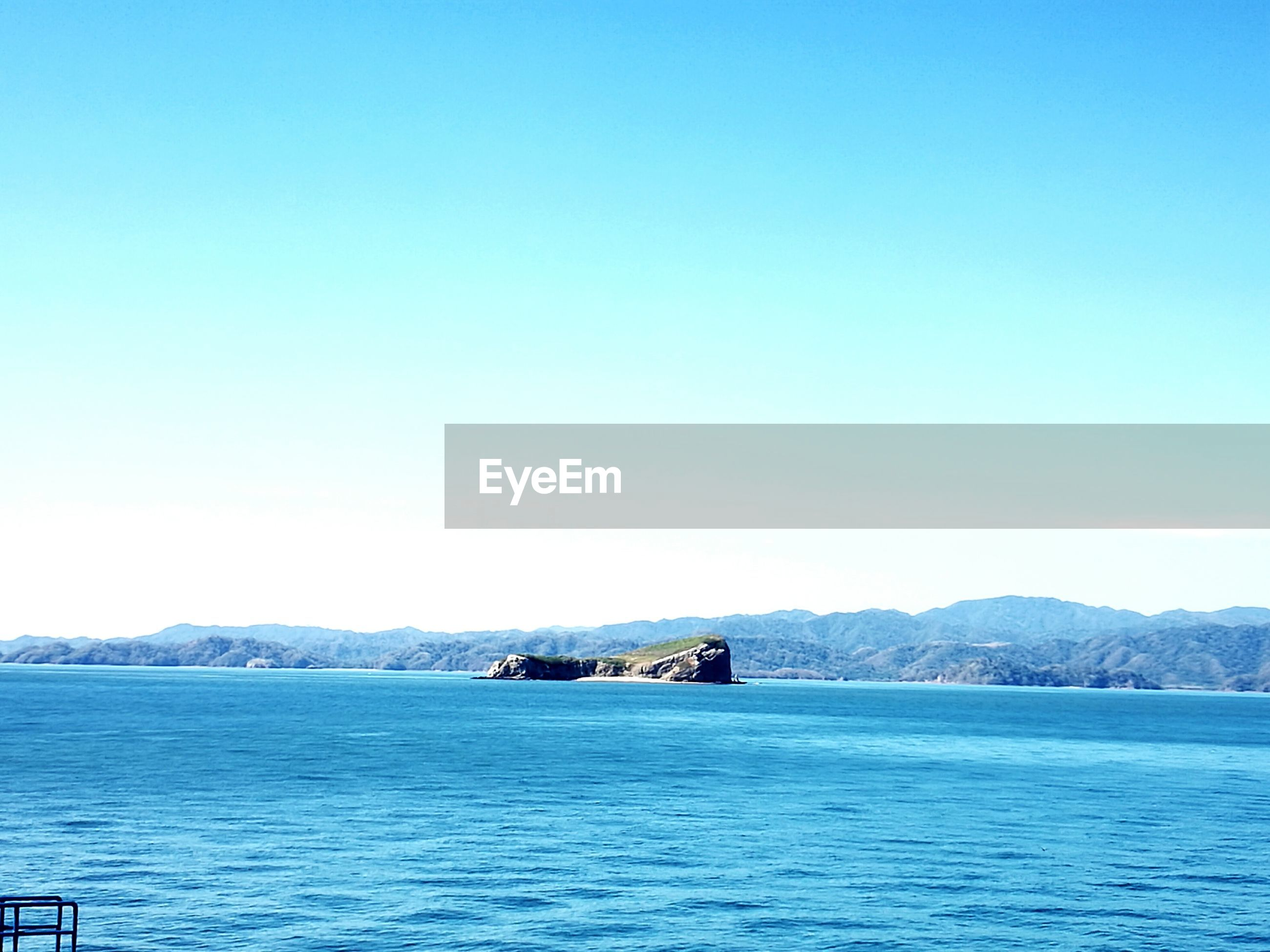 copy space, scenics, beauty in nature, blue, nature, water, sea, tranquil scene, no people, tranquility, clear sky, outdoors, day, waterfront, mountain, sky