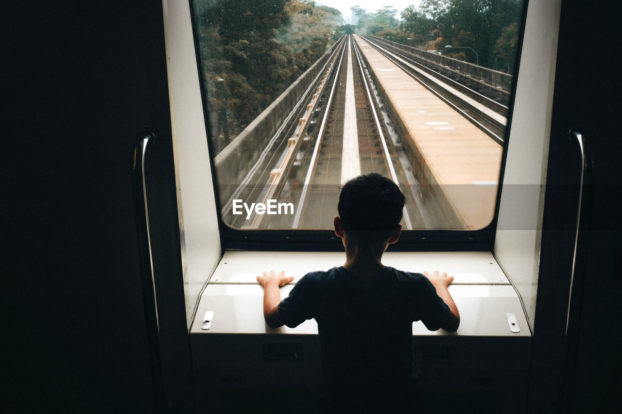 Rear View Of Boy Looking Through Window In Train