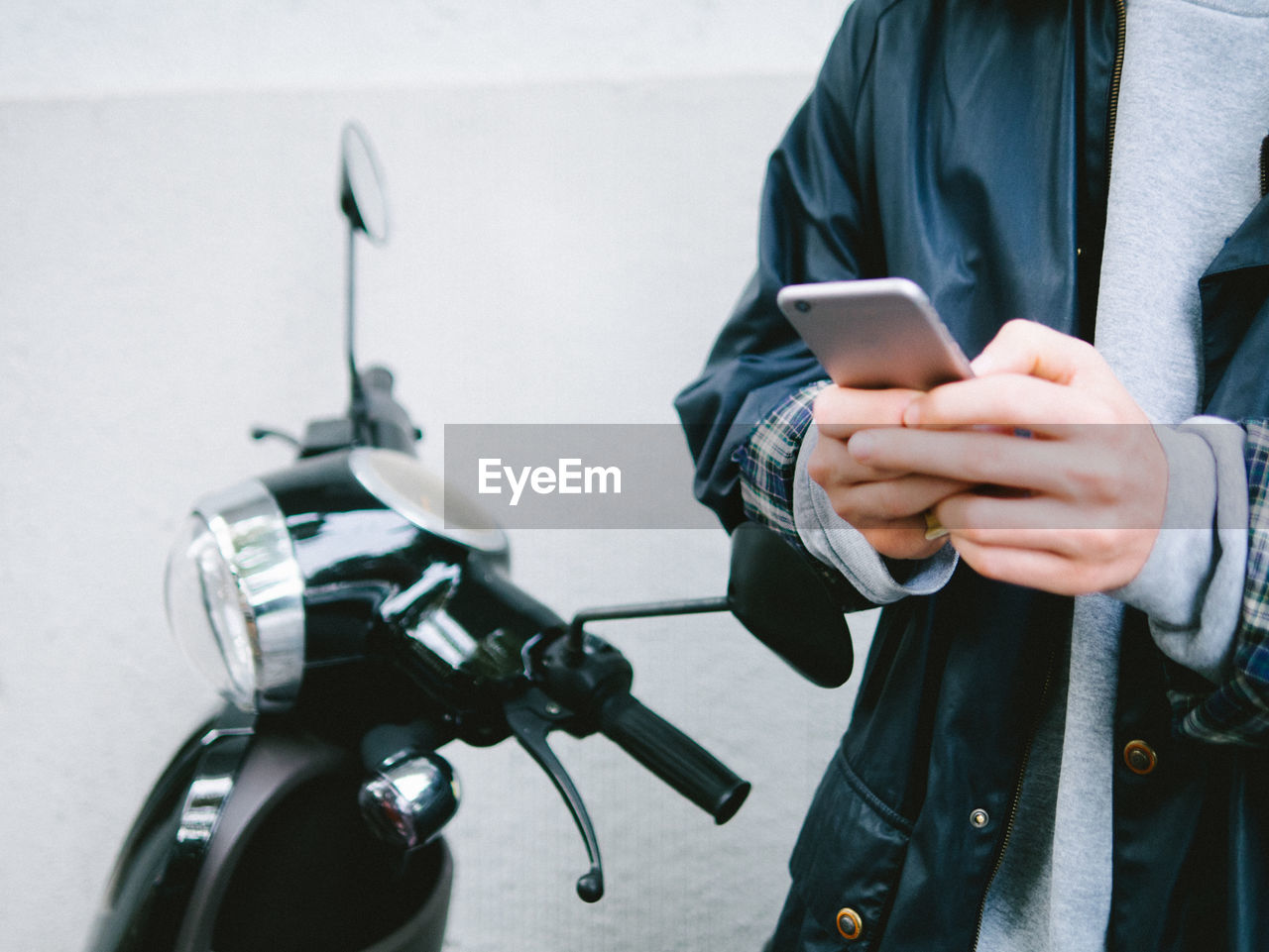 Midsection Of Man Using Mobile Phone By Scooter
