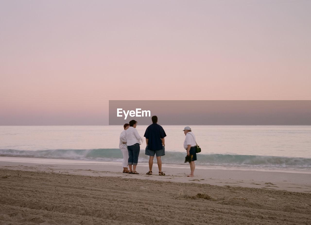 COUPLE WALKING ON BEACH AGAINST CLEAR SKY