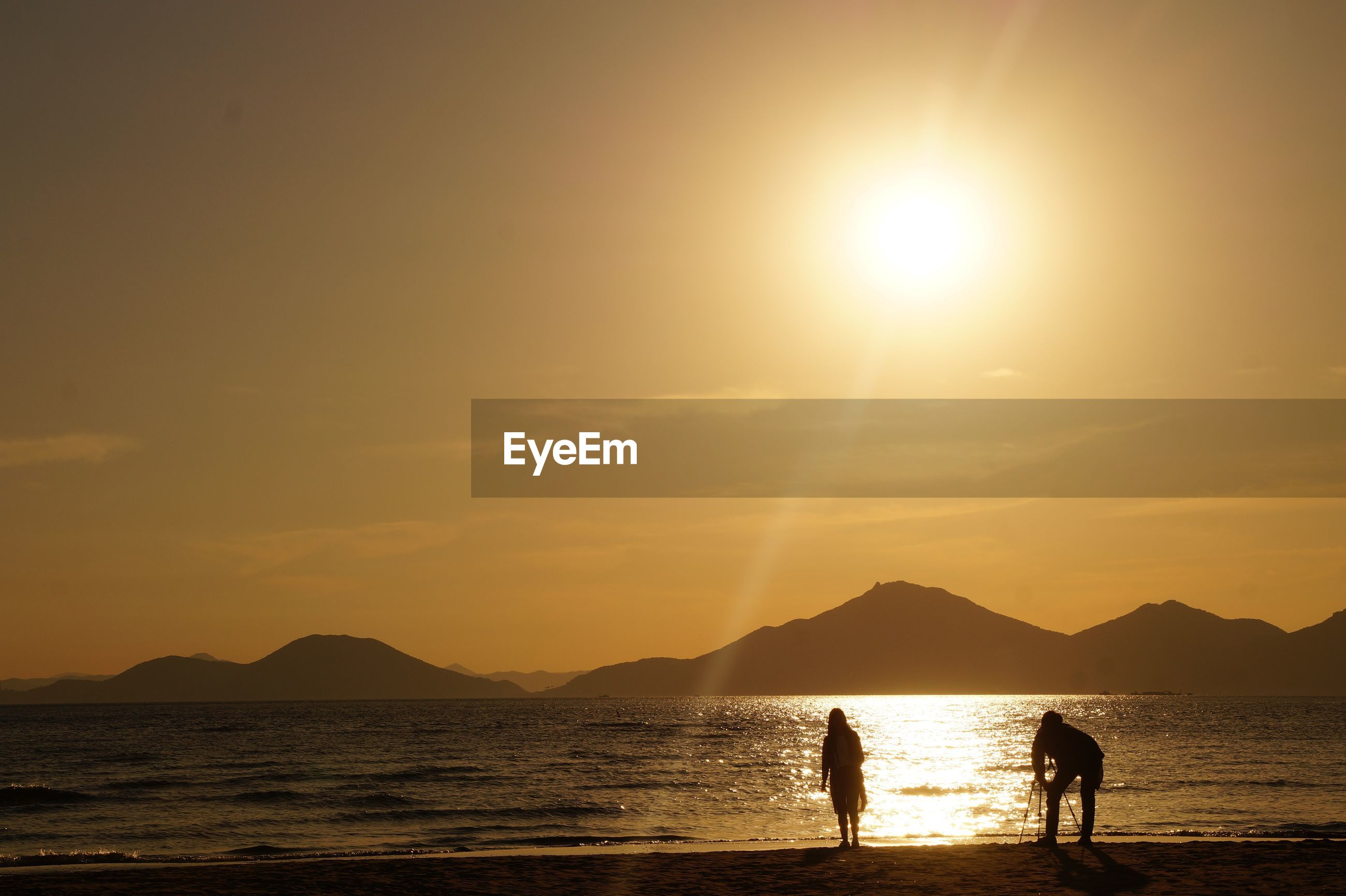 sunset, sun, silhouette, beauty in nature, nature, scenics, sea, water, sky, two people, sunbeam, real people, sunlight, beach, leisure activity, tranquility, lifestyles, tranquil scene, men, outdoors, horizon over water, togetherness, vacations, mountain, people