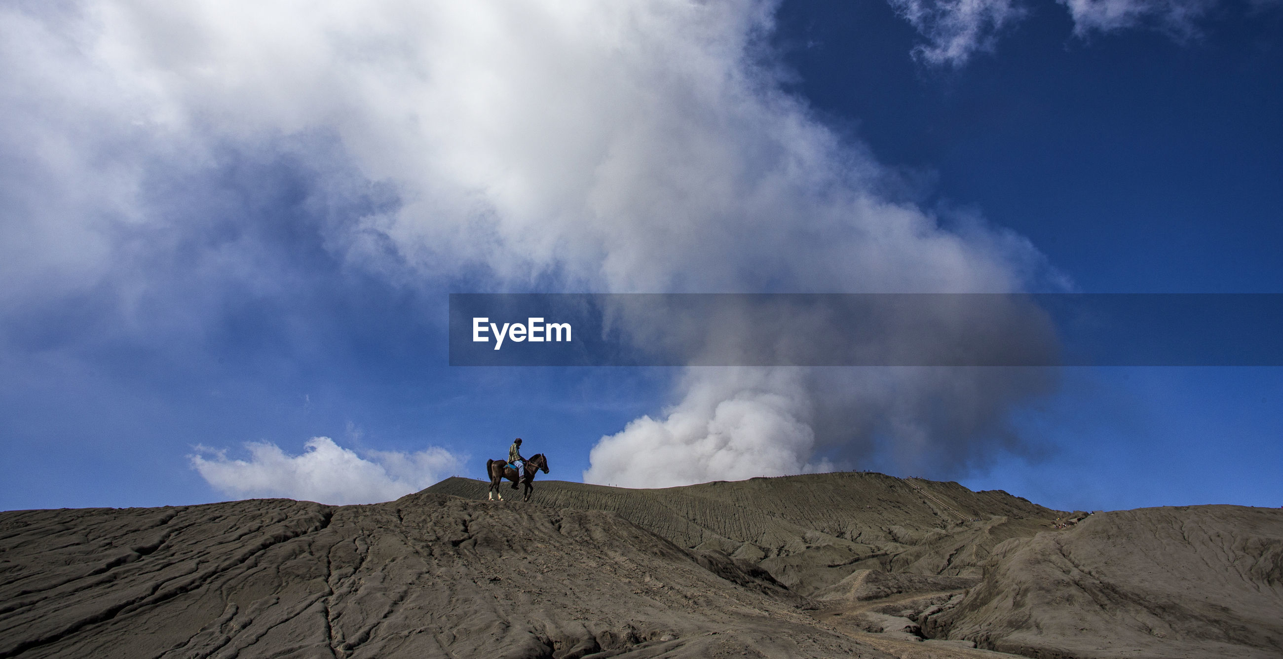Mid distance view of person riding horse at mt bromo against blue sky