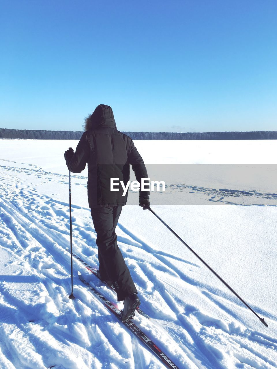 Person skiing on snow covered landscape against clear blue sky