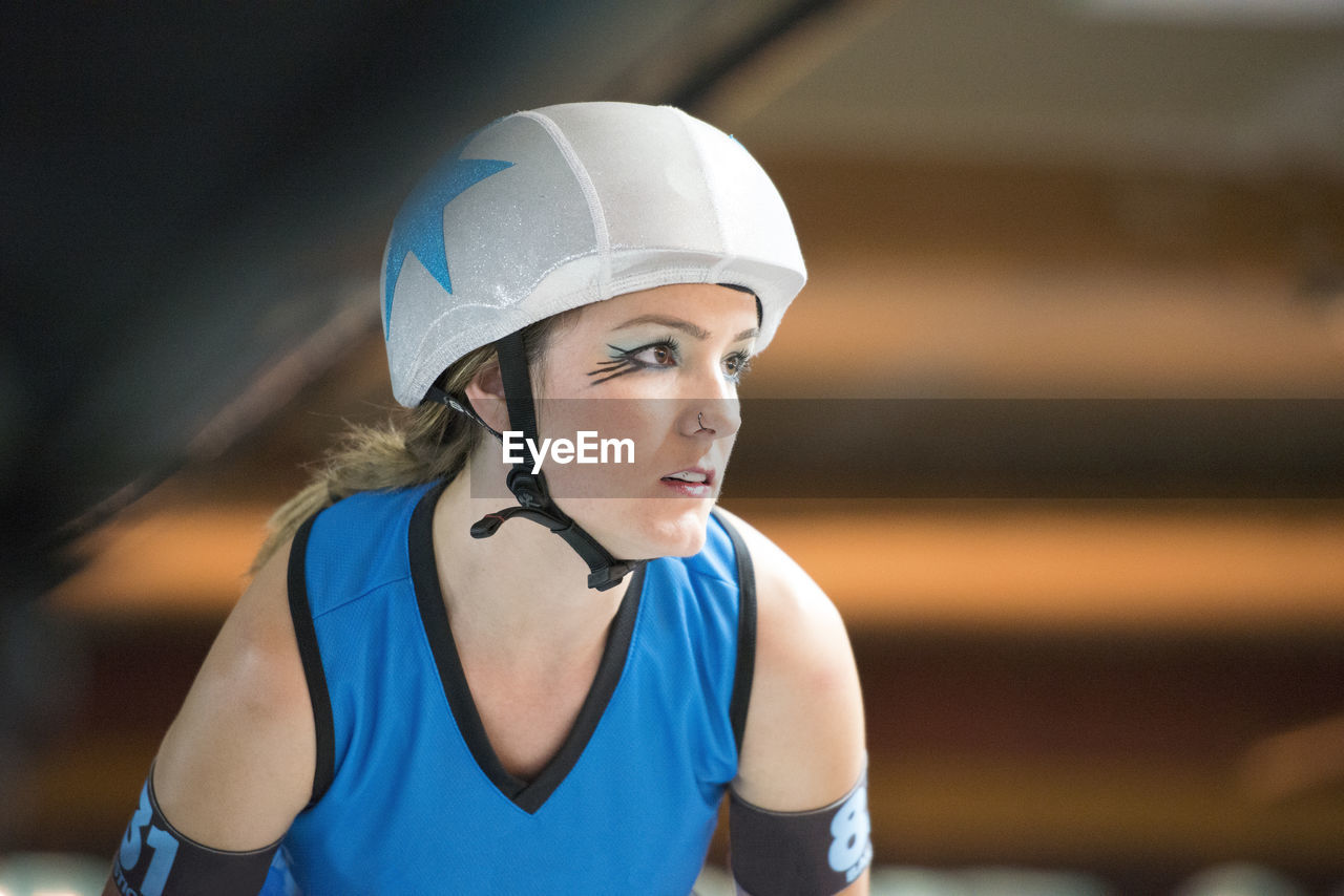 one person, focus on foreground, portrait, real people, young adult, lifestyles, blue, headwear, helmet, sports clothing, leisure activity, front view, looking away, clothing, standing, young women, sport