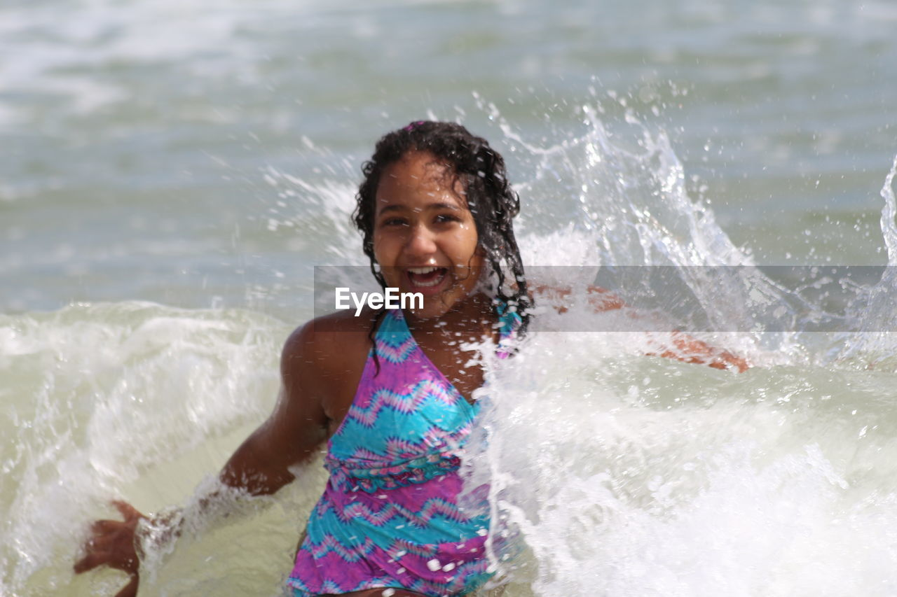 water, motion, happiness, smiling, one person, fun, real people, splashing, front view, leisure activity, looking at camera, lifestyles, cheerful, sea, outdoors, enjoyment, elementary age, portrait, day, vacations, childhood, sunlight, young adult, standing, young women, nature, wave, people