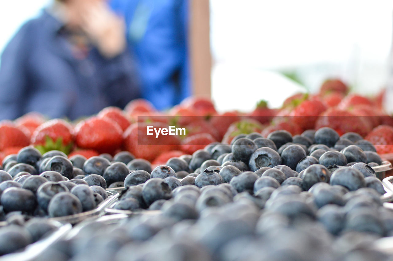 fruit, food and drink, healthy eating, food, freshness, wellbeing, selective focus, berry fruit, red, one person, real people, day, market, blueberry, large group of objects, close-up, market stall, healthy lifestyle, retail, for sale, ripe, antioxidant