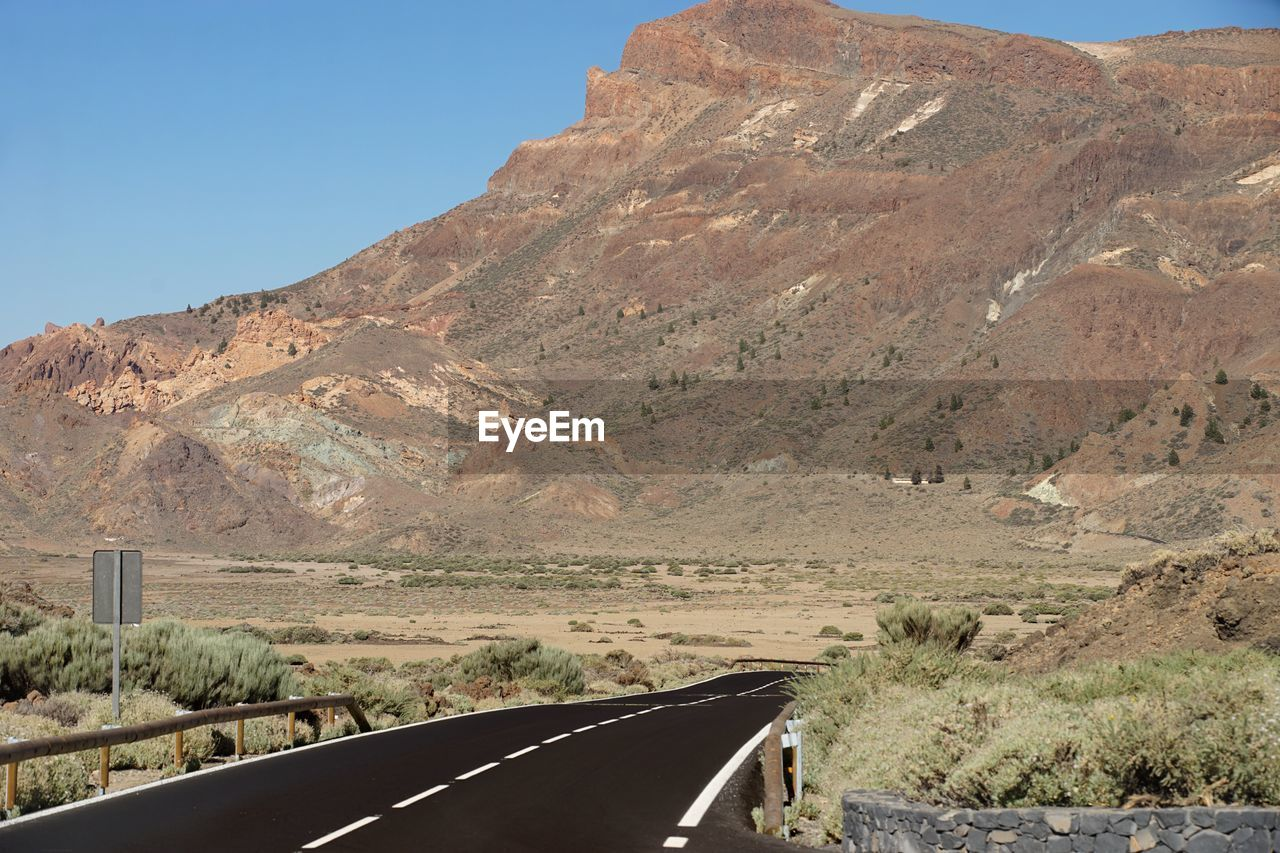 mountain, transportation, mode of transportation, environment, car, landscape, scenics - nature, mountain range, day, road, nature, motor vehicle, beauty in nature, sky, land vehicle, no people, non-urban scene, vehicle interior, transparent, tranquility, outdoors, formation, arid climate, climate