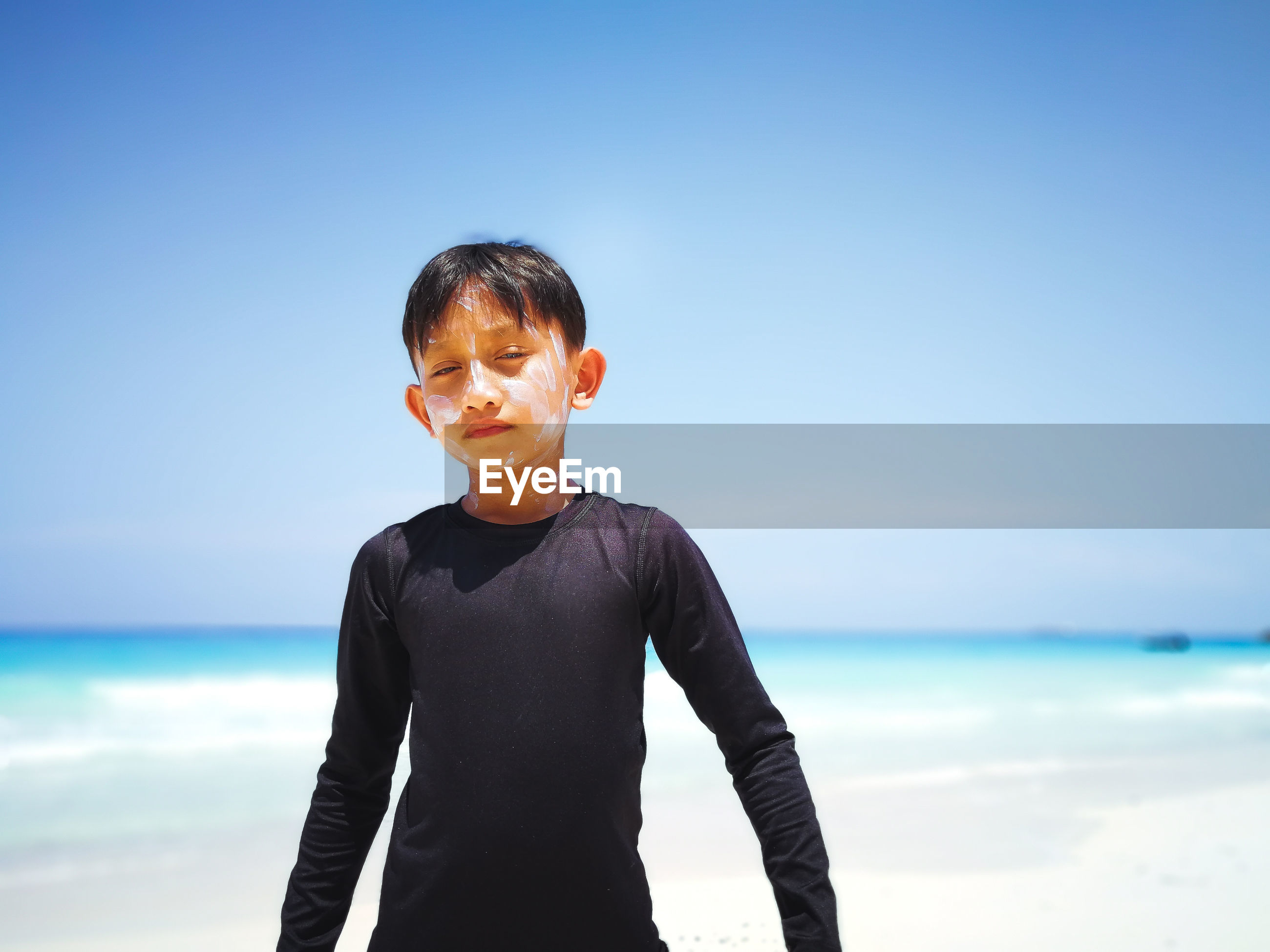 Boy standing on beach against sky
