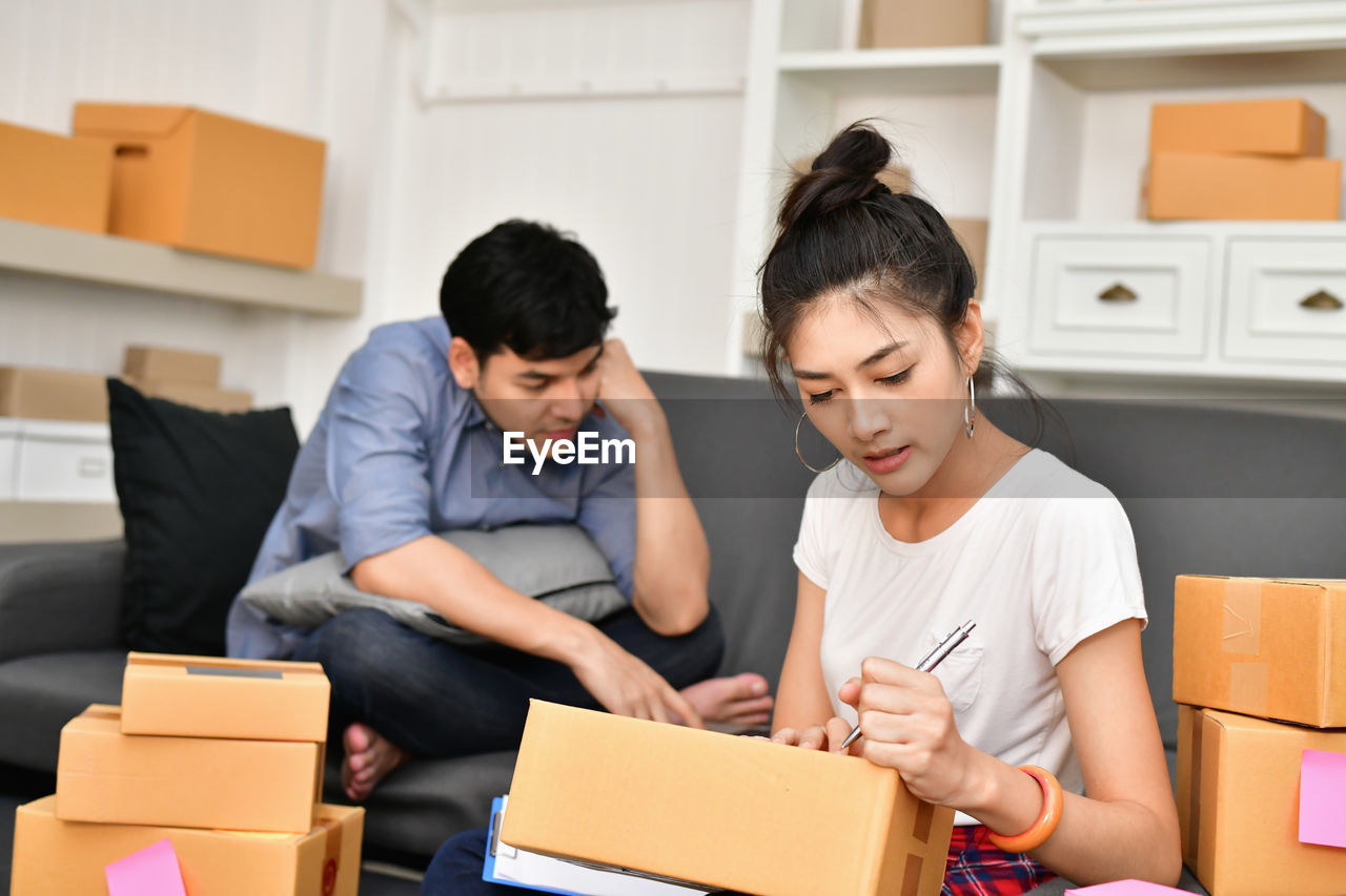 two people, indoors, real people, women, adult, young adult, young women, sitting, front view, casual clothing, lifestyles, people, focus on foreground, togetherness, looking, young men, holding, box, men, box - container