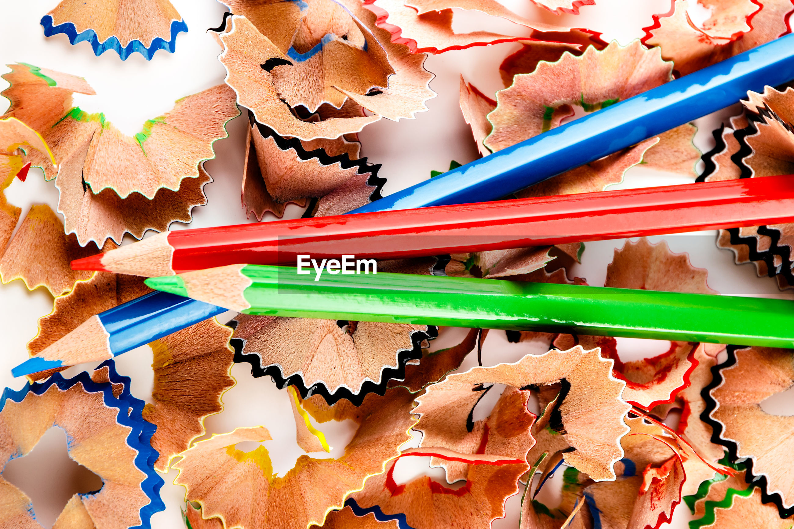 High angle view of multi colored pencils and shavings against white background