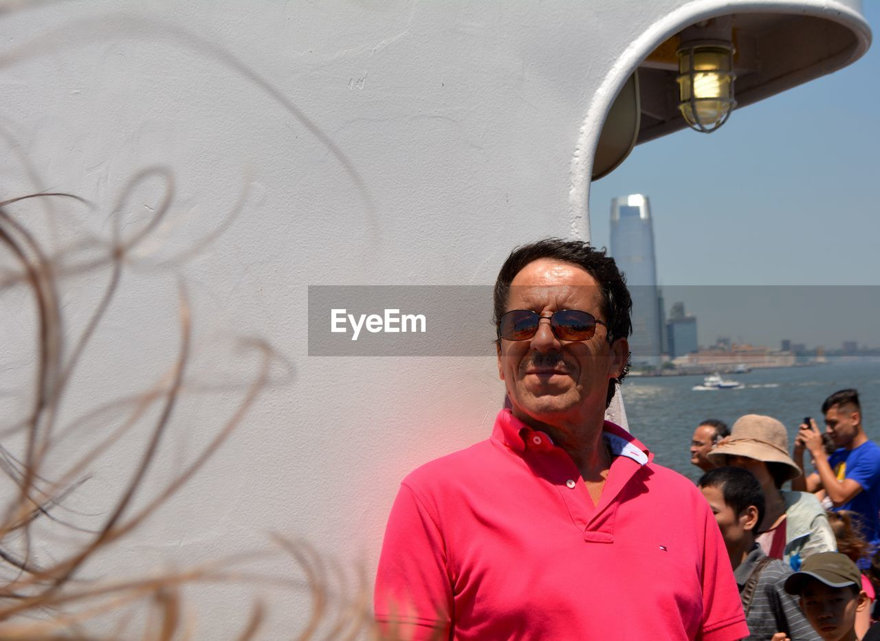 Smiling senior man wearing sunglasses while standing against wall