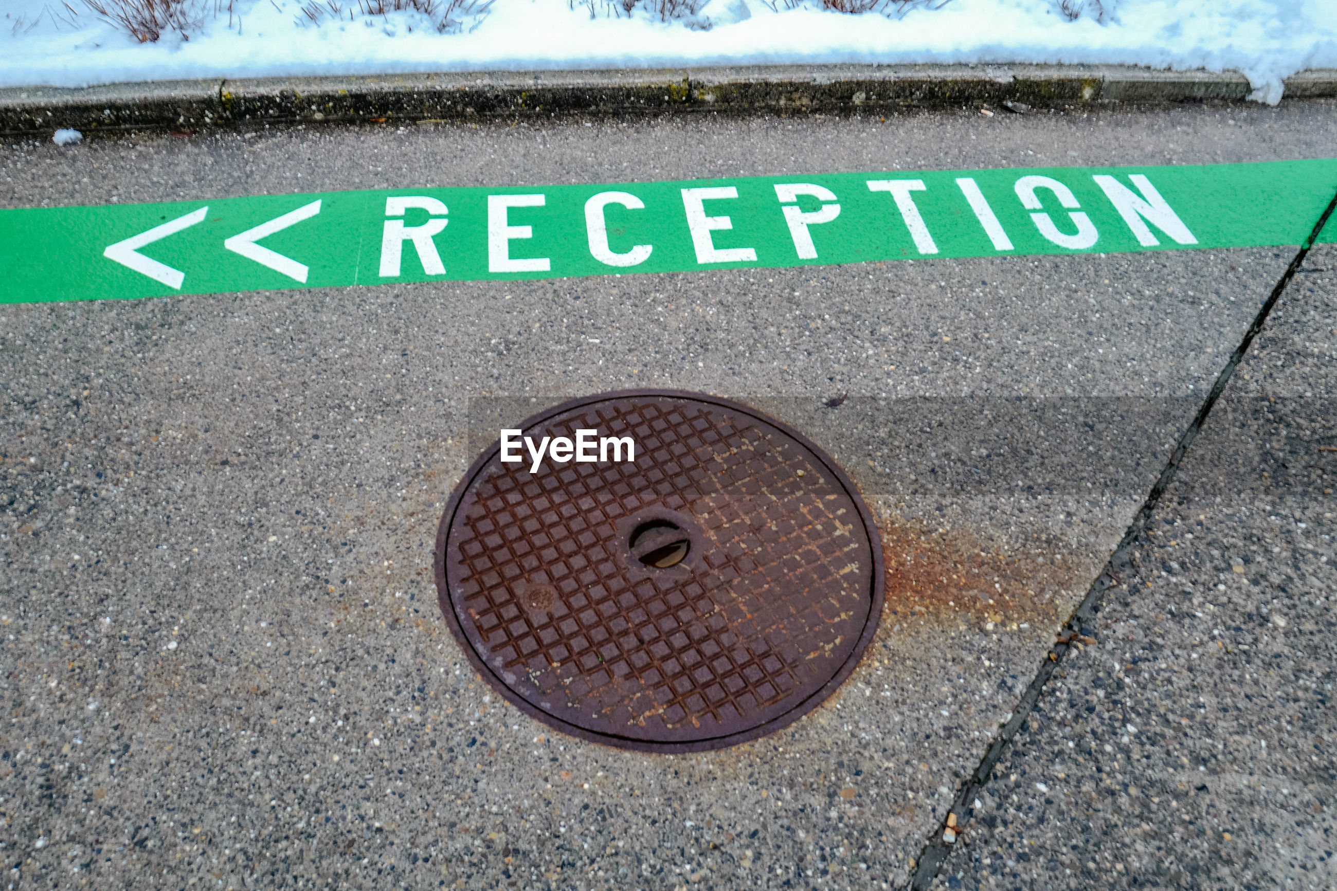 High angle view of reception text by manhole lid on footpath