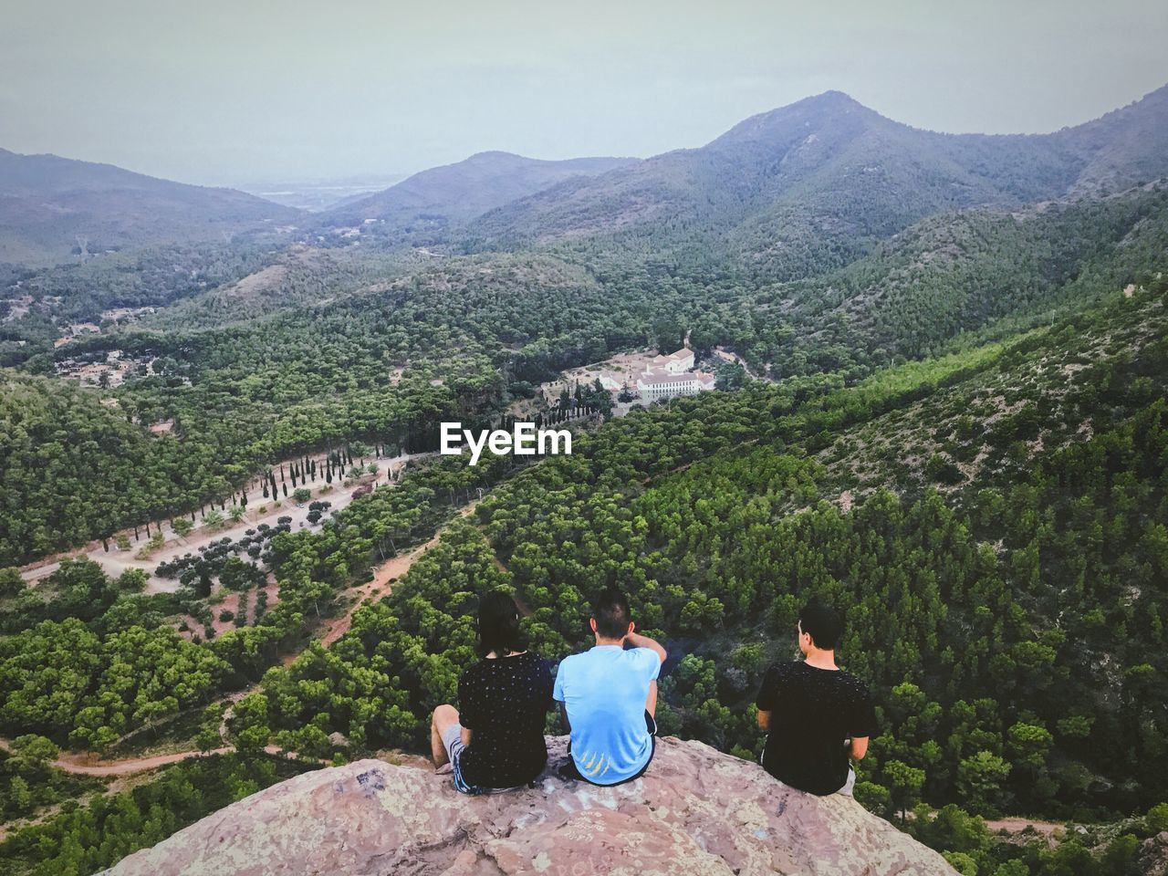 Male And Female Friends Sitting On Mountain Overlooking Landscape