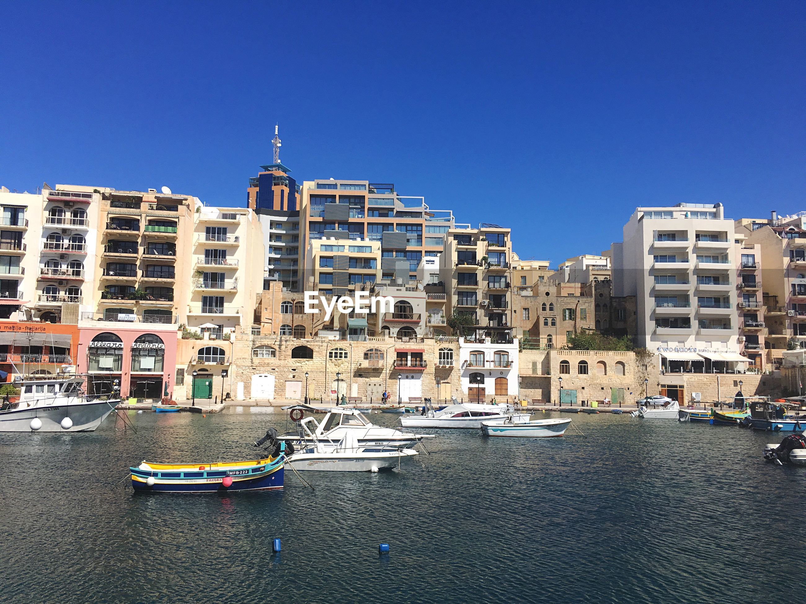 Boats moored at harbor in sea by city against clear blue sky