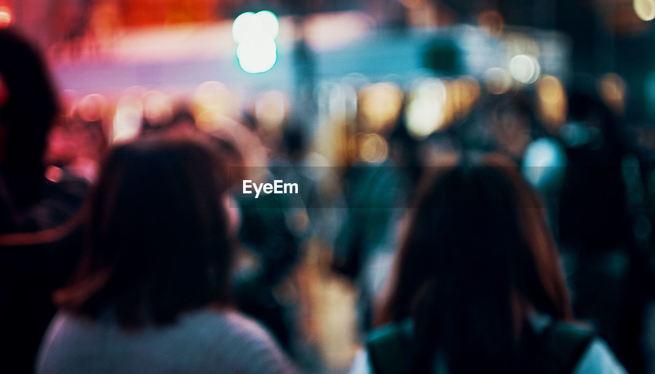 Defocused image of women standing in city at night
