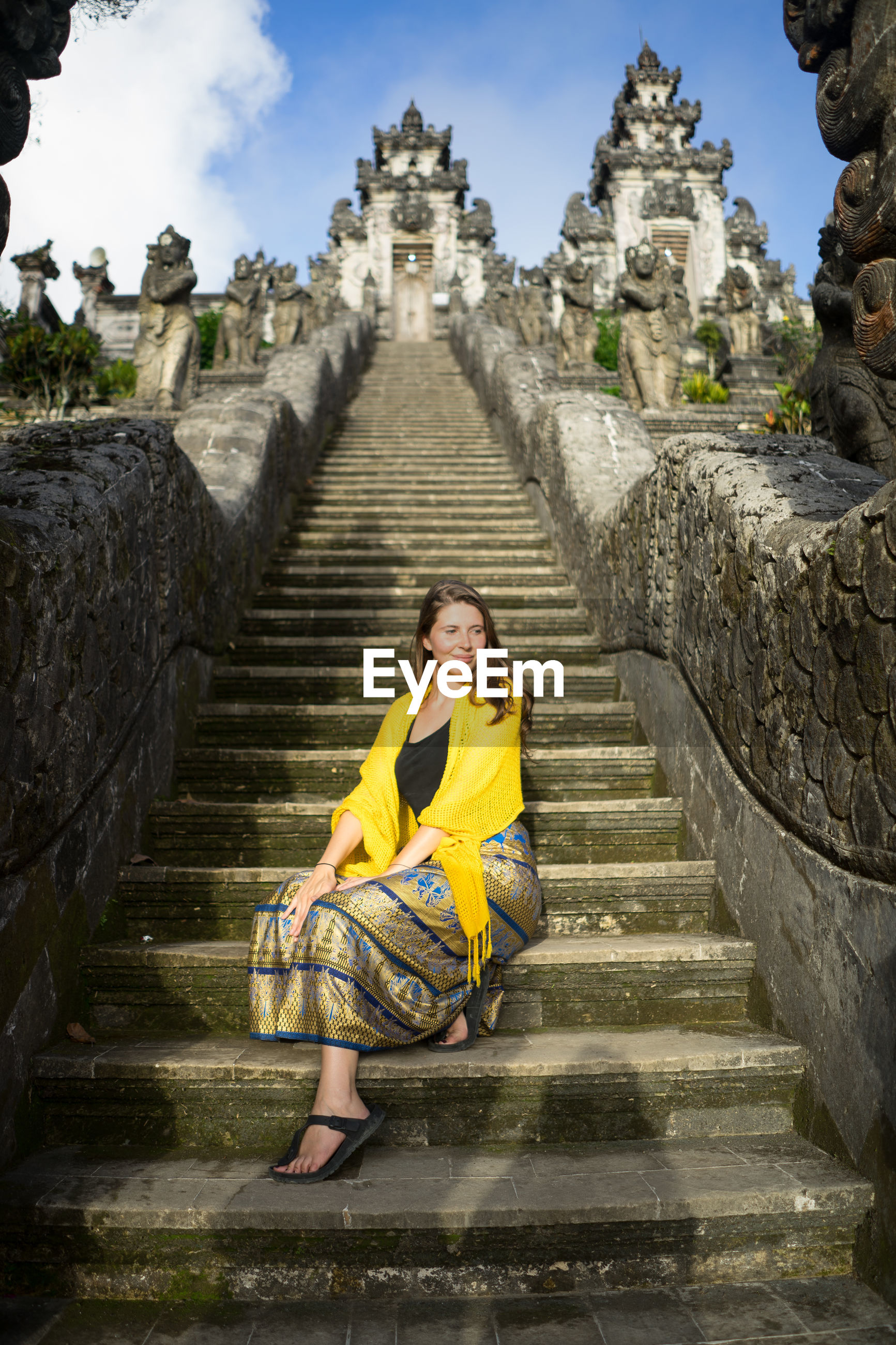 Woman sitting on staircase against old temples