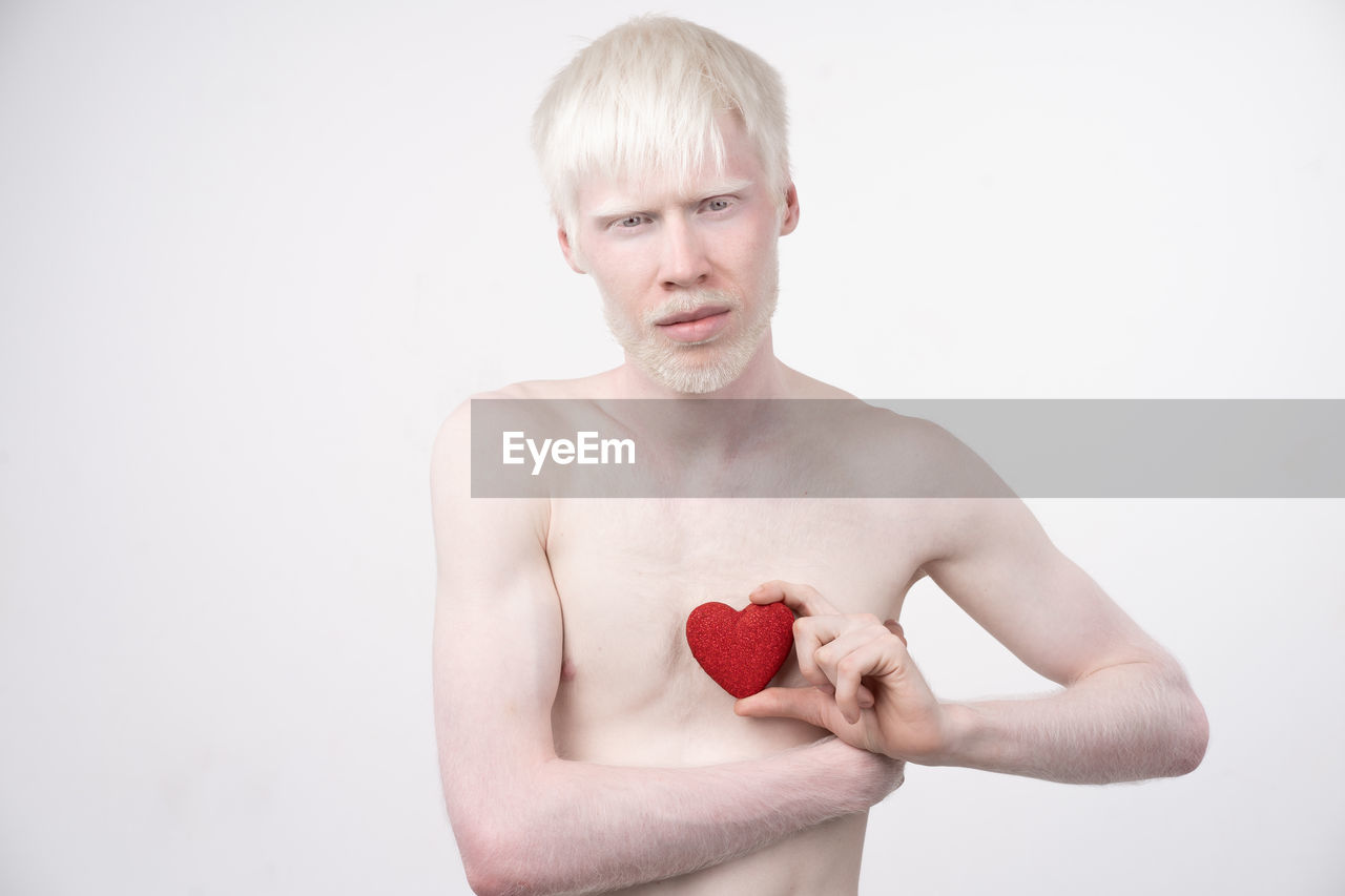Portrait of shirtless man holding heart shape against white background