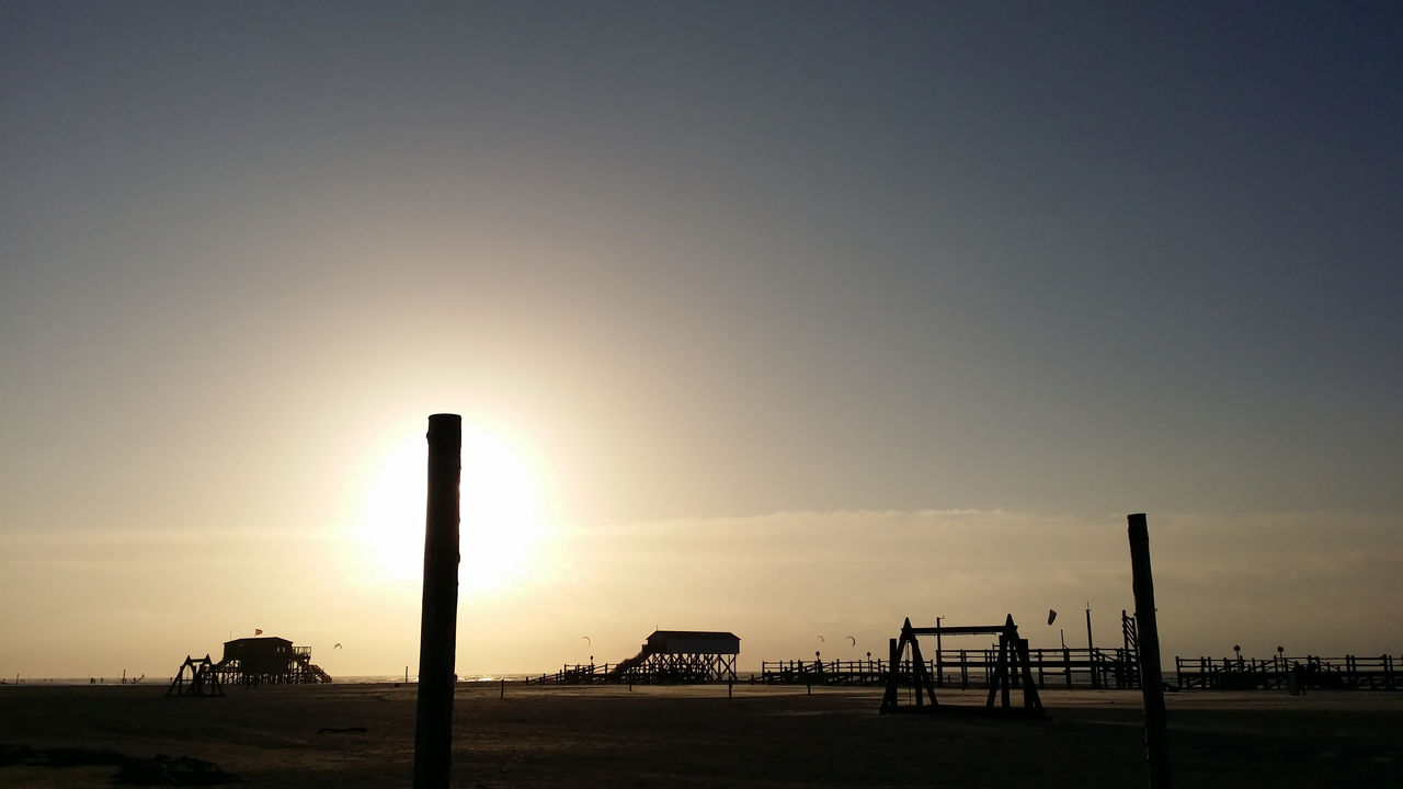 sky, sunset, silhouette, nature, copy space, land, beauty in nature, built structure, scenics - nature, architecture, no people, outdoors, clear sky, water, beach, industry, tranquil scene, sun, field, tranquility, wooden post