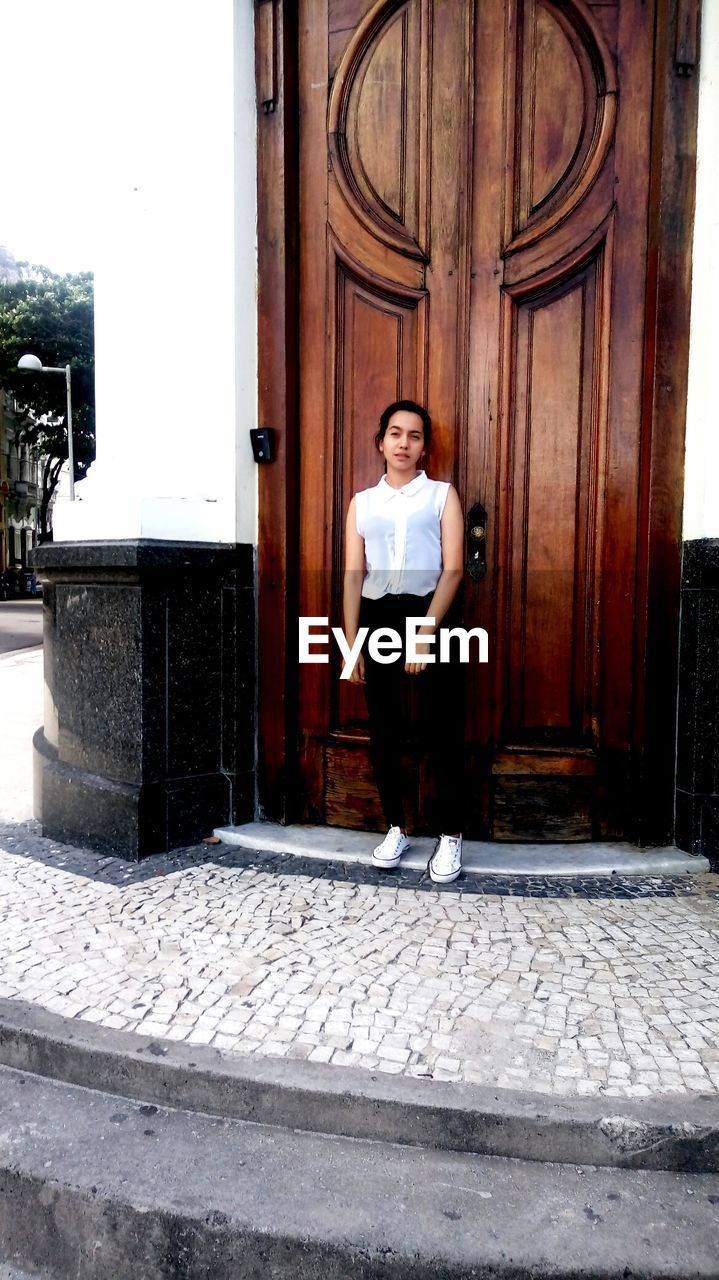 young adult, young women, portrait, door, full length, front view, standing, one person, looking at camera, real people, beautiful woman, confidence, day, doorway, outdoors, building exterior, architecture, smiling, lifestyles, built structure, happiness, one young woman only, adult, people