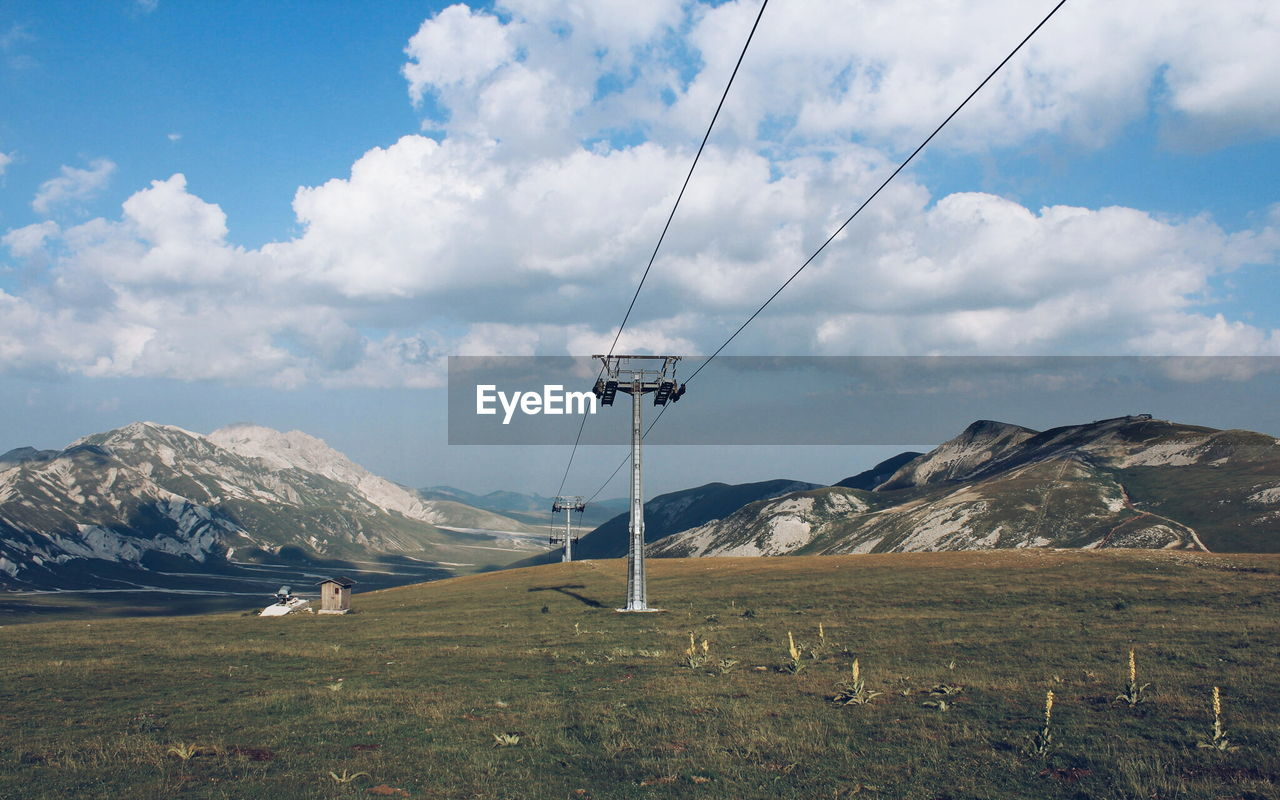 Low Angle View Of Overhead Cable Car Against Mountains And Cloudy Sky