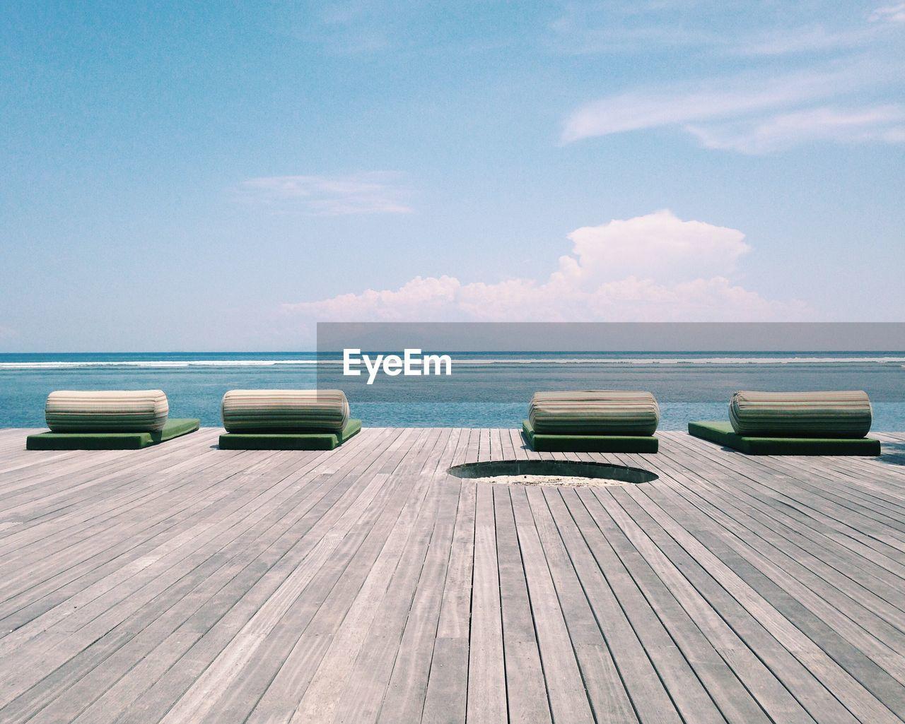 Seats On Boardwalk By Sea Against Sky