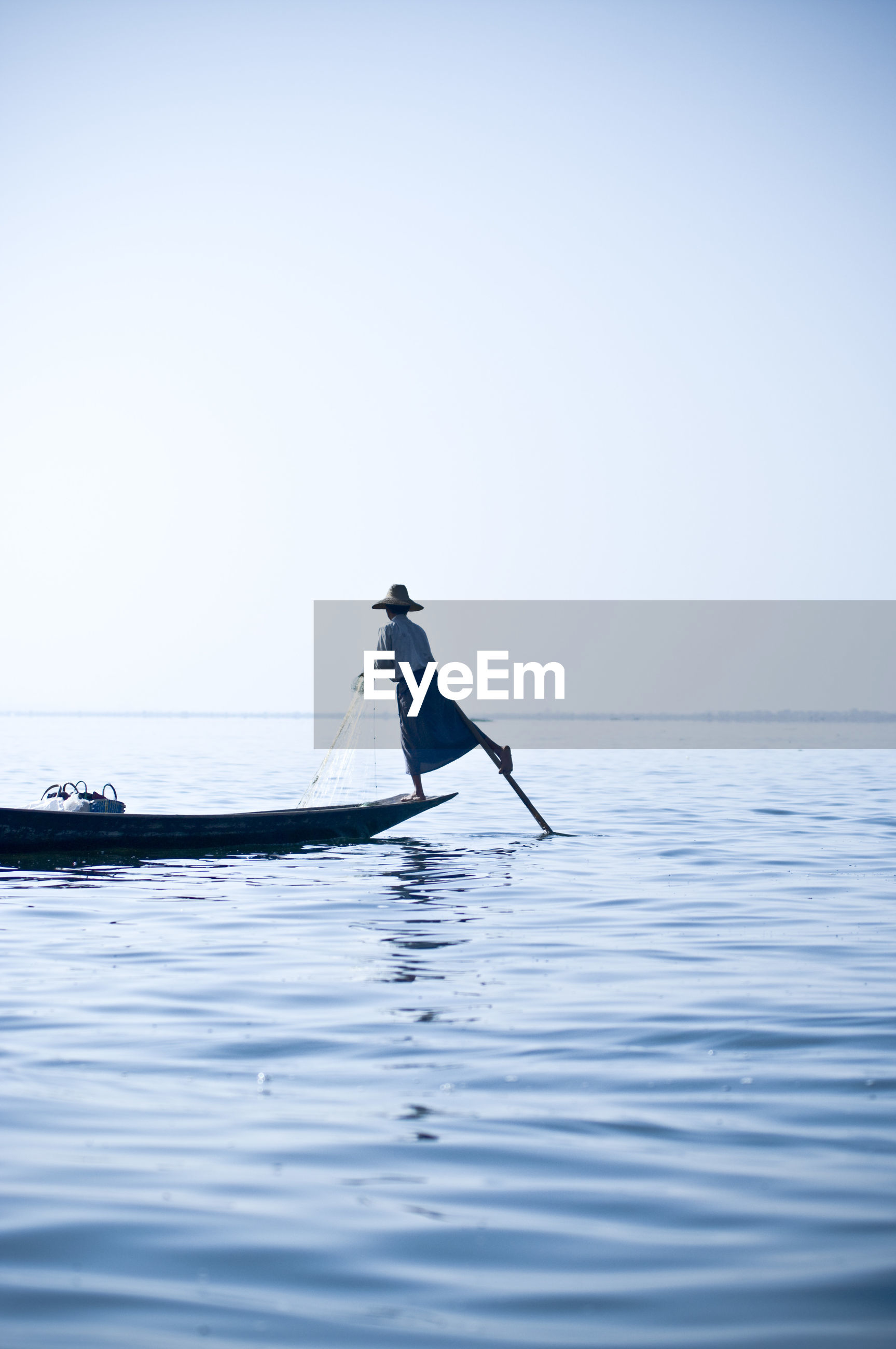 Rear view of man standing in fishing boat