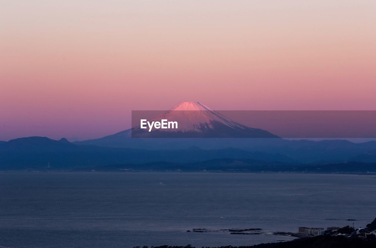mountain, scenics - nature, beauty in nature, sky, tranquil scene, tranquility, sunset, idyllic, volcano, no people, non-urban scene, water, nature, orange color, copy space, land, travel destinations, remote, mountain peak, snowcapped mountain