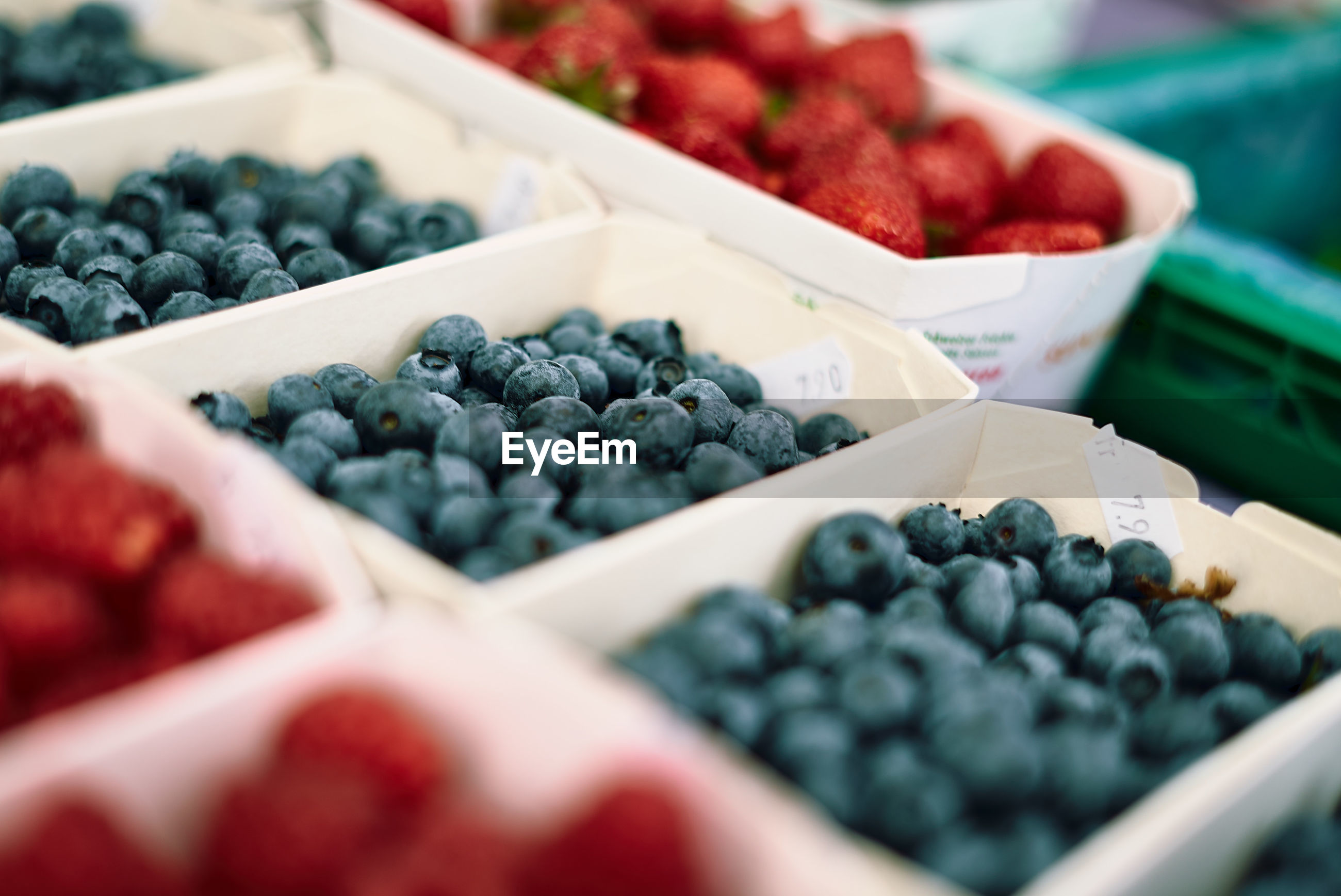 Close-up of berry fruits in container at market stall