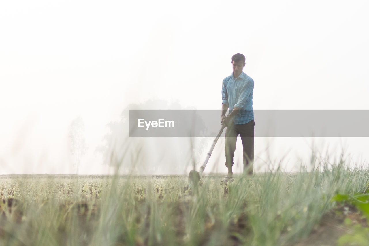 leisure activity, casual clothing, one person, real people, outdoors, grass, standing, day, lifestyles, nature, clear sky, golf, men, golf course, water, sky, golfer