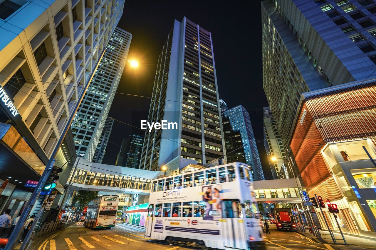 architecture, illuminated, building exterior, built structure, city, night, building, modern, city life, street, office building exterior, transportation, incidental people, tall - high, low angle view, sky, motion, skyscraper, blurred motion, outdoors