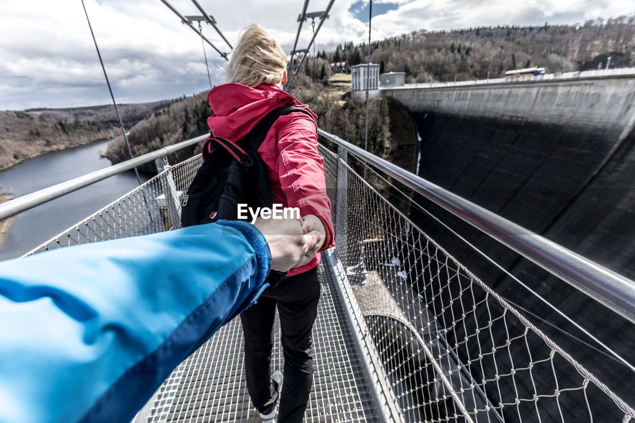 real people, railing, one person, transportation, water, day, lifestyles, rear view, nature, connection, leisure activity, bridge, casual clothing, three quarter length, women, adult, nautical vessel, red, outdoors, bridge - man made structure, footbridge, warm clothing