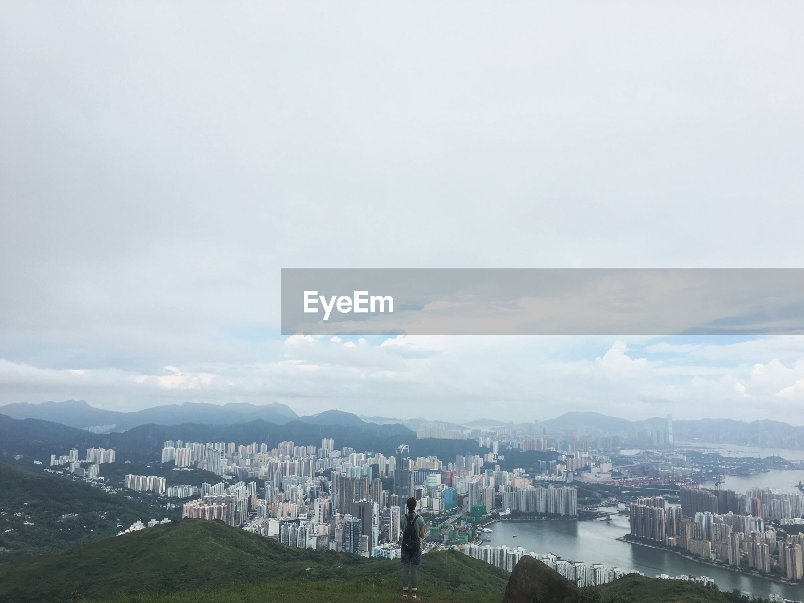 Rear view of woman standing on hill while looking at cityscape against sky