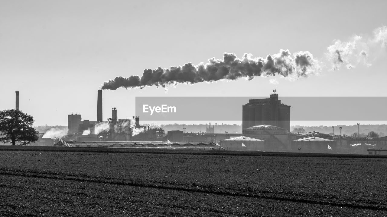 building exterior, smoke - physical structure, pollution, sky, factory, smoke stack, built structure, architecture, emitting, industry, environmental issues, environment, air pollution, nature, day, chimney, no people, smoke, fumes, tall - high, atmospheric, outdoors, ecosystem, cooling tower