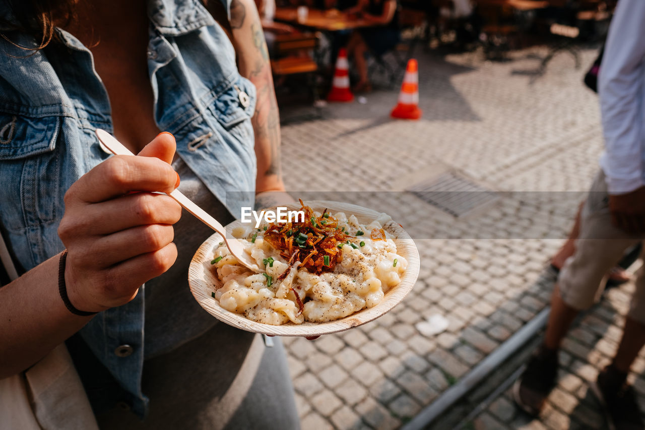 Midsection Of Woman Eating Food Outdoors