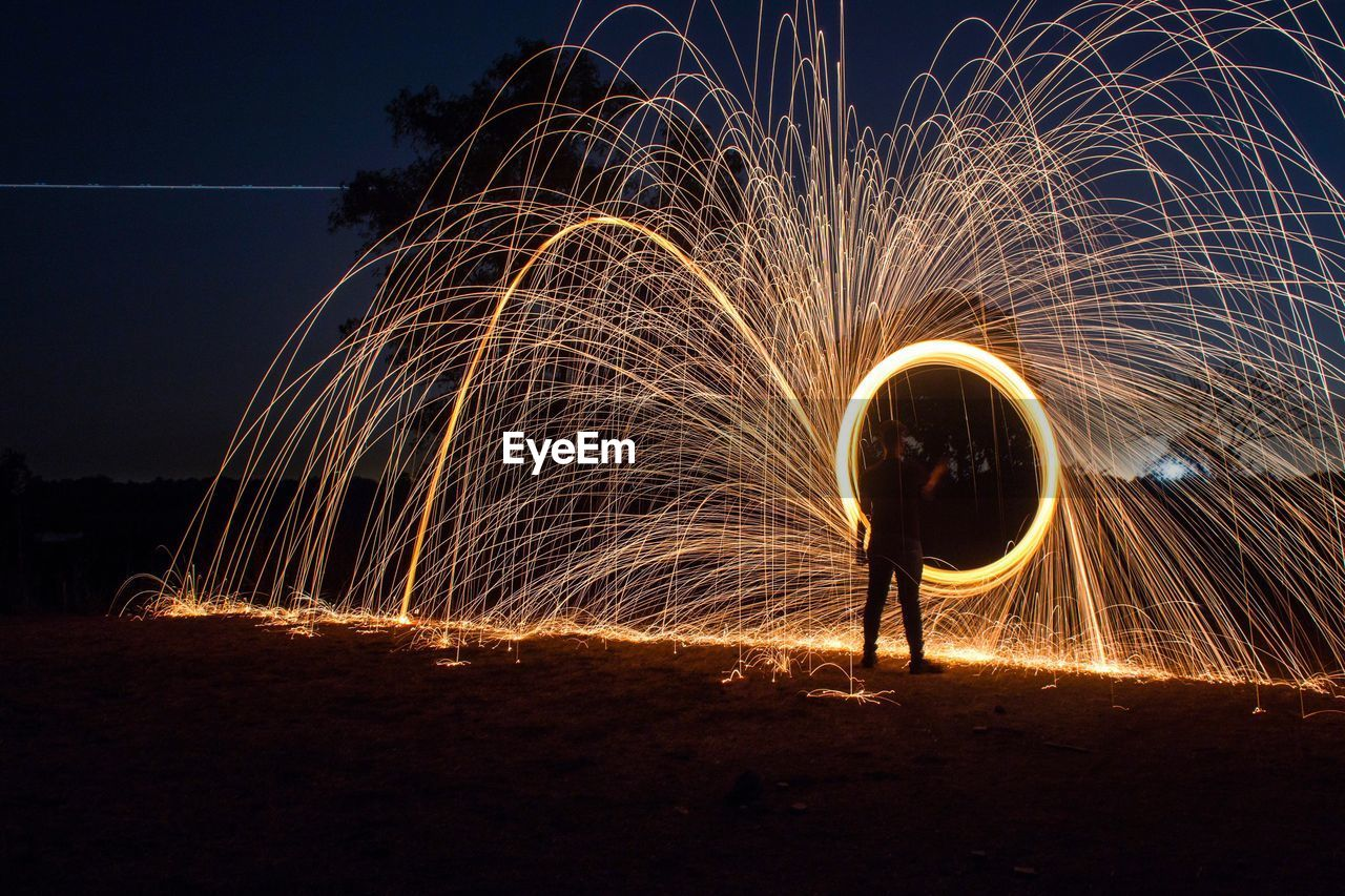 Rear View Of Man Light Painting