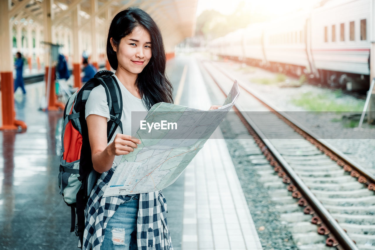rail transportation, one person, looking at camera, transportation, standing, focus on foreground, portrait, holding, young adult, travel, real people, railroad track, track, hair, smiling, long hair, front view, lifestyles, hairstyle, outdoors