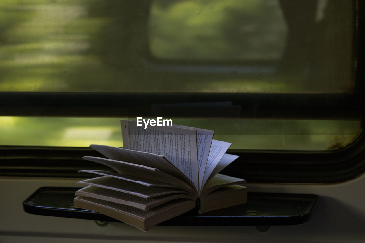 Close-up of open book on table in train