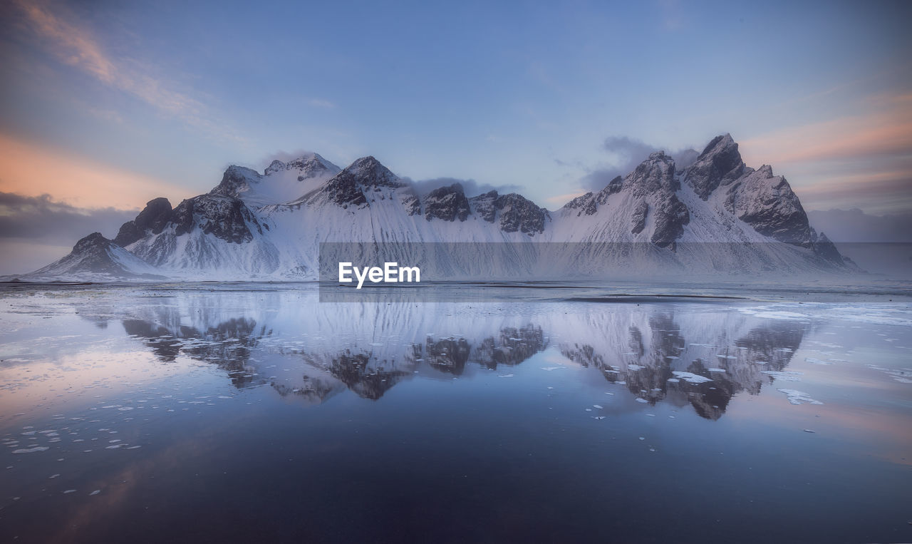 Scenic view of lake by snowcapped mountain against sky during sunset