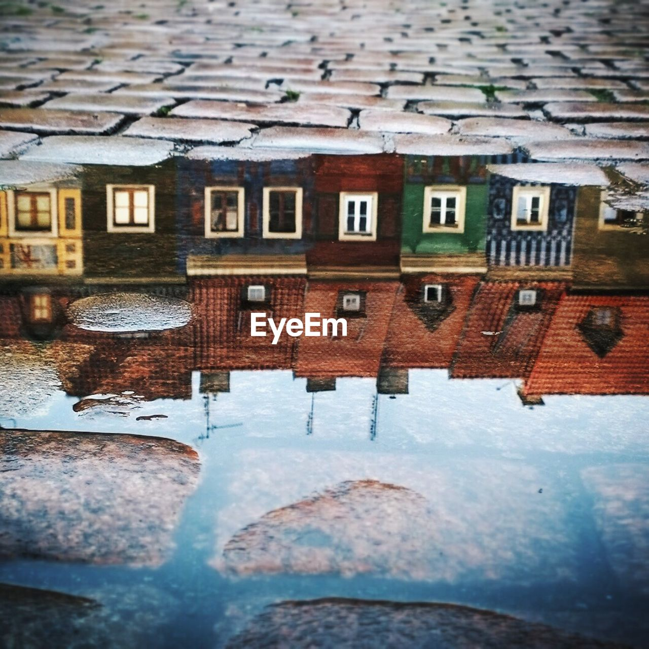 Reflection of colorful houses on puddle