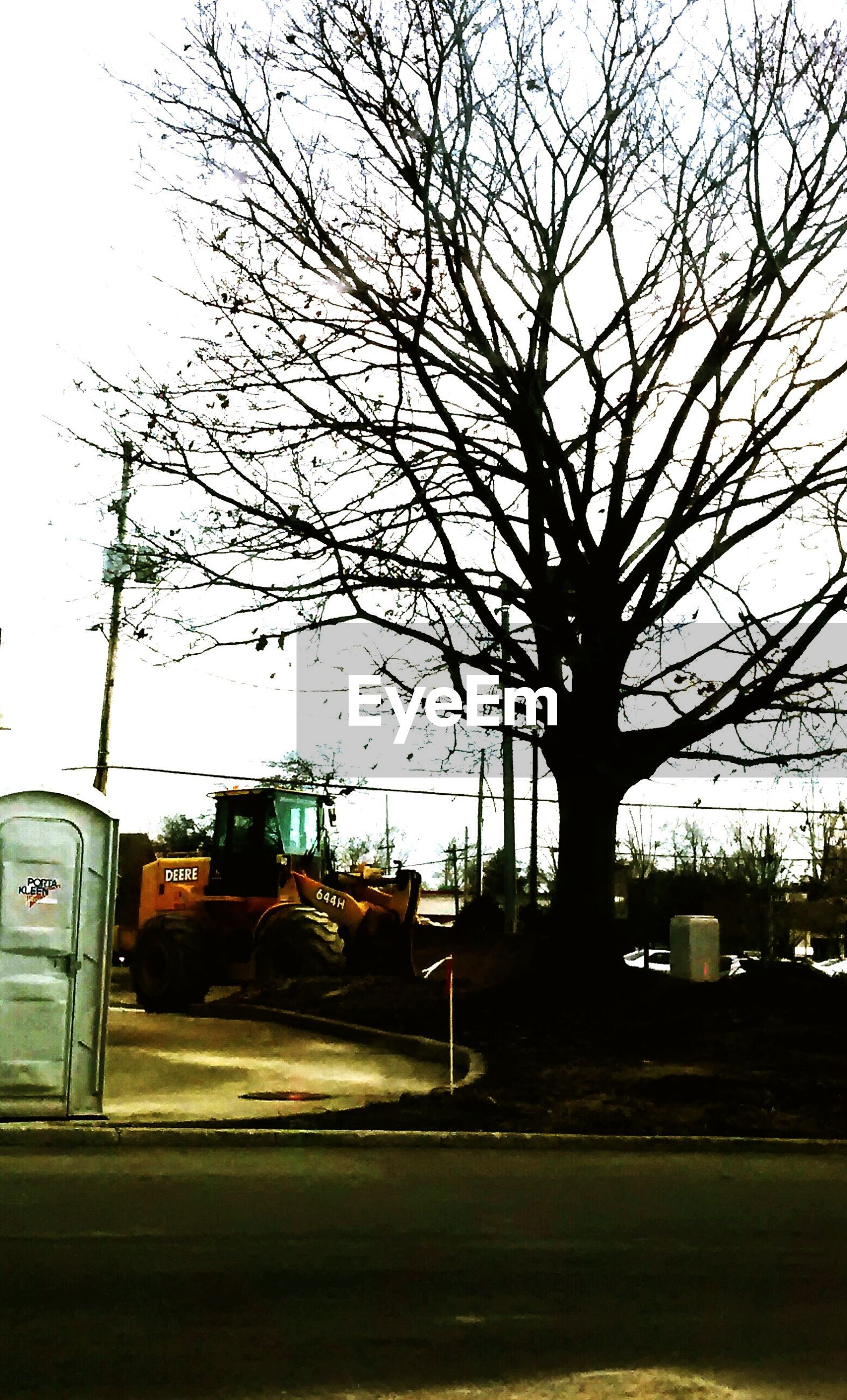 bare tree, building exterior, transportation, car, tree, built structure, architecture, land vehicle, street, mode of transport, road, sky, clear sky, street light, city, silhouette, branch, outdoors, no people, sunlight
