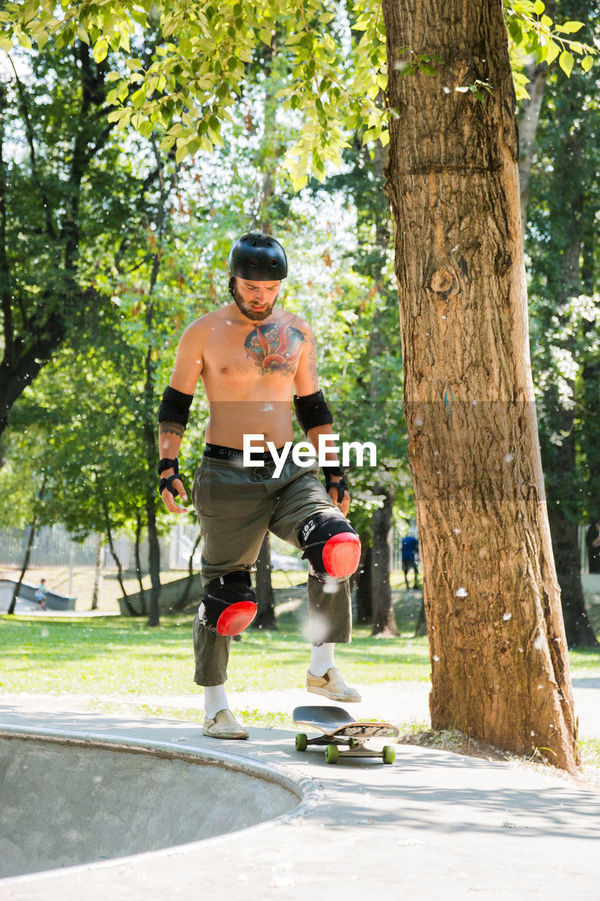 tree, full length, plant, one person, leisure activity, sport, day, nature, casual clothing, tree trunk, trunk, front view, men, shadow, sports equipment, sunlight, lifestyles, fun, outdoors, shorts
