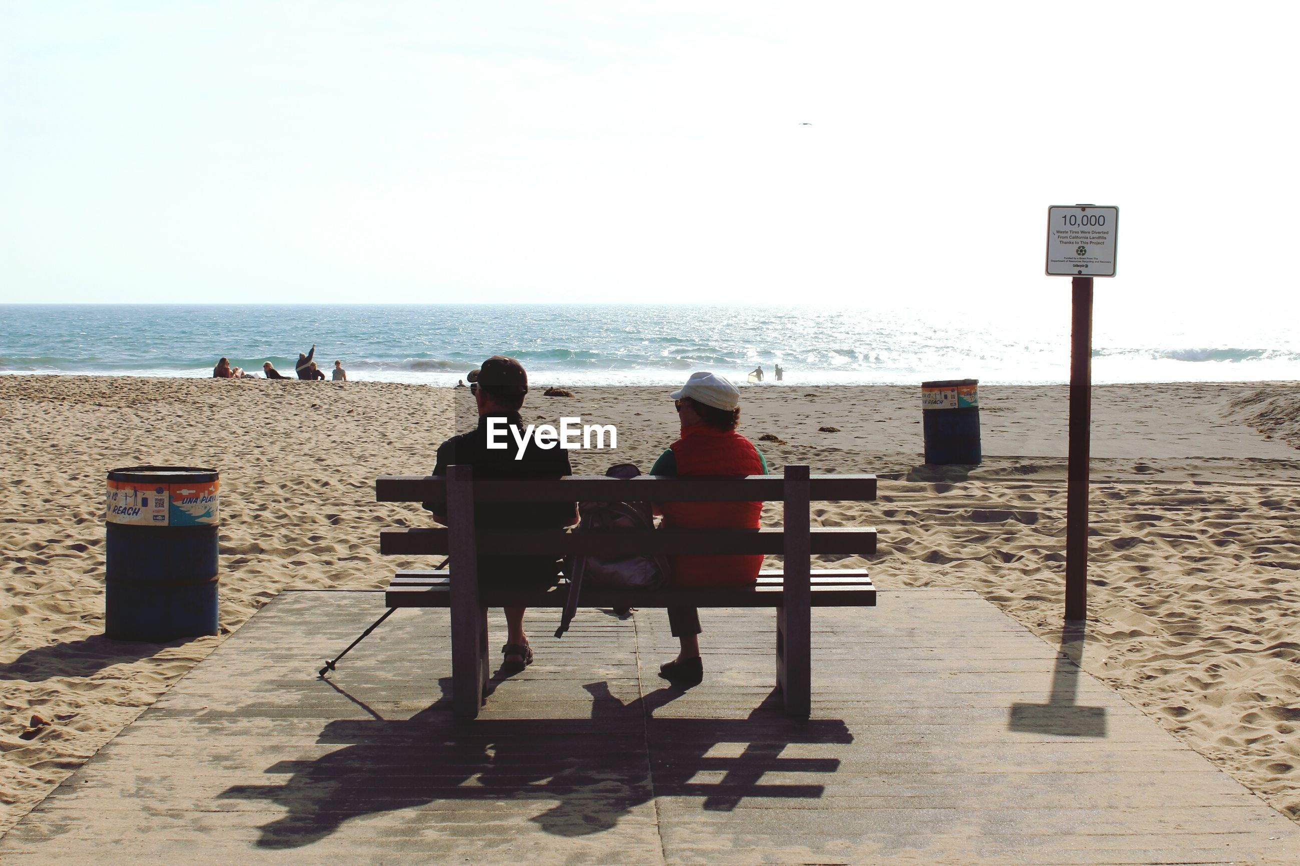 Friends sitting on bench at beach