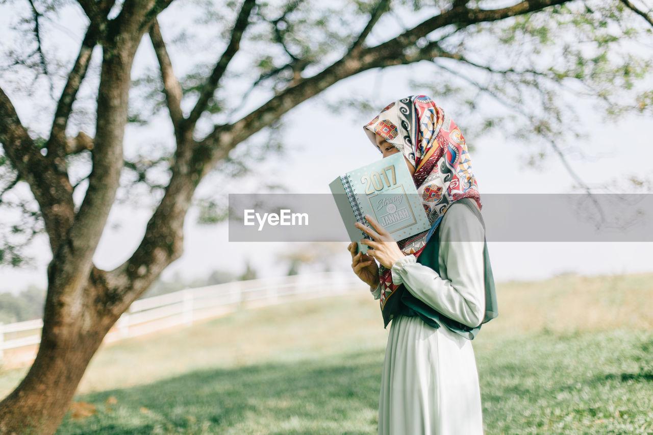 WOMAN HOLDING UMBRELLA AGAINST TREES