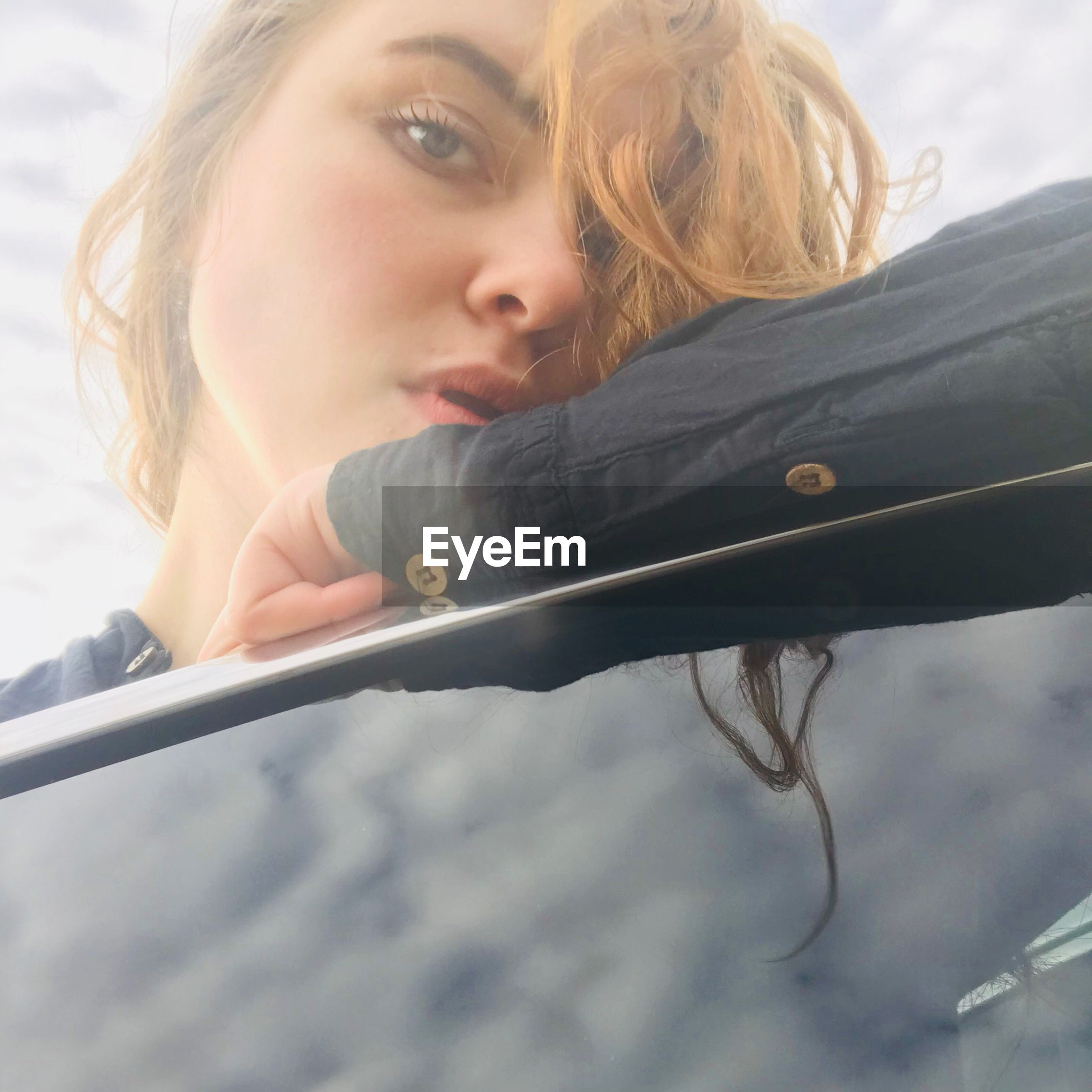 Low angle portrait of woman leaning on car window
