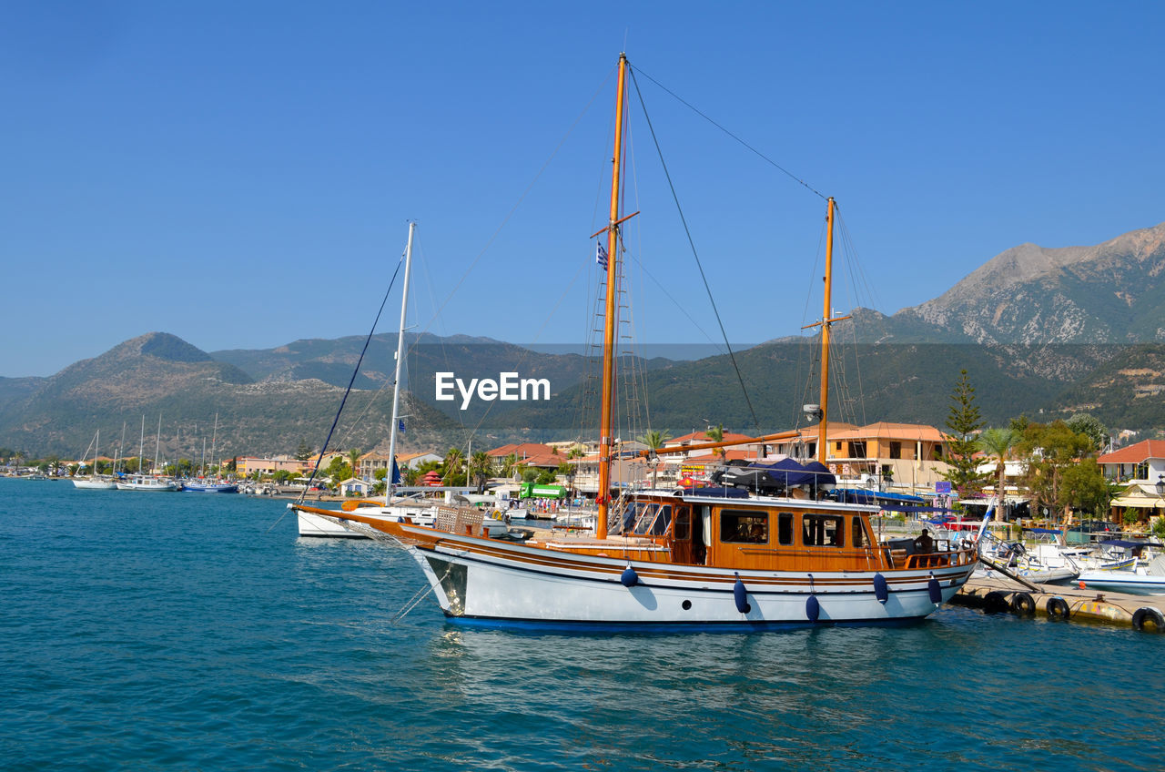 Sailboats moored at harbor by mountain against clear blue sky