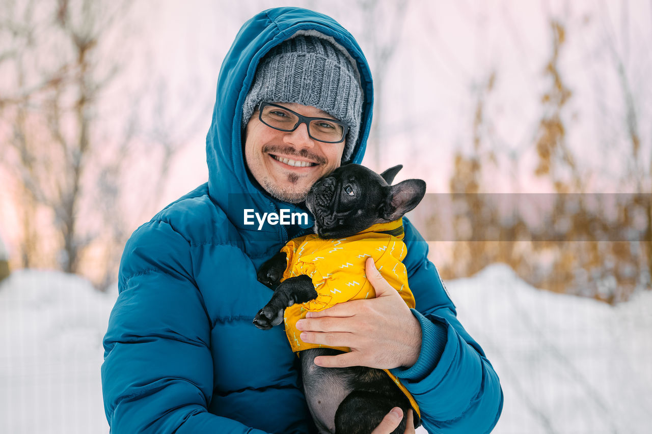 Portrait Of Smiling Man Carrying Dog In Forest During Winter