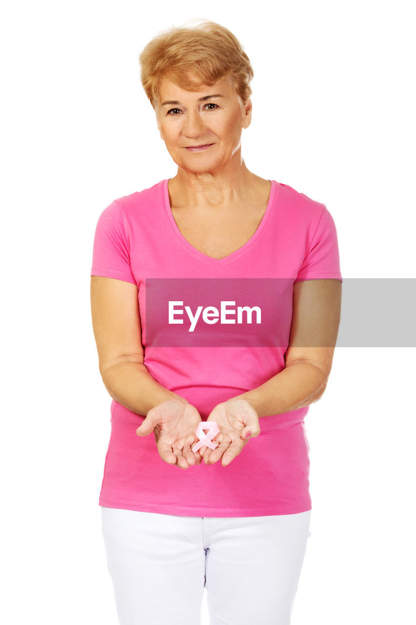 Confident Senior Woman With Breast Cancer Awareness Ribbon Against White Background