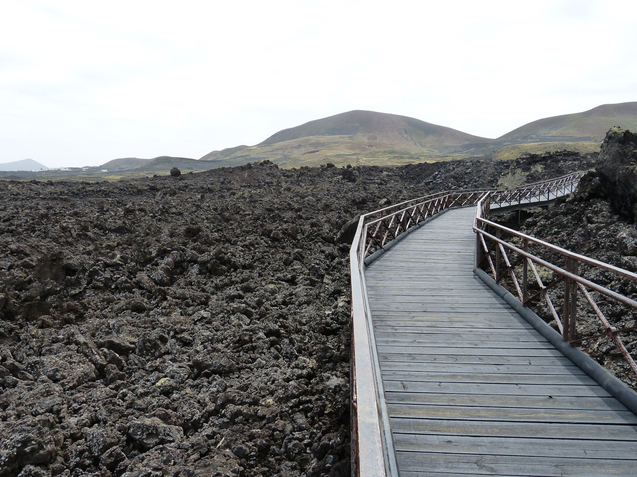 Boardwalk on barren landscape against clear sky