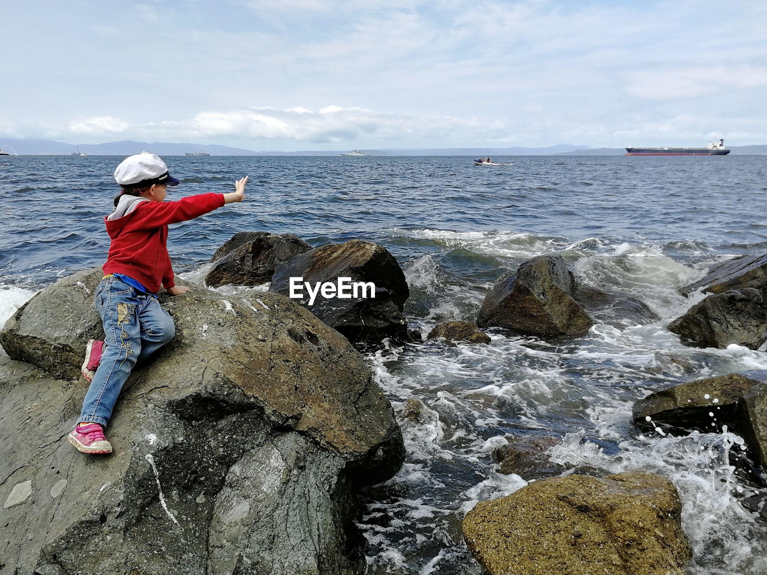 Girl sitting on rock on shore against sky